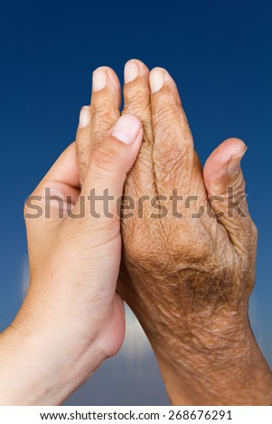 Hands and held her granddaughter holding hands with the sky as a backdrop. - stock photo