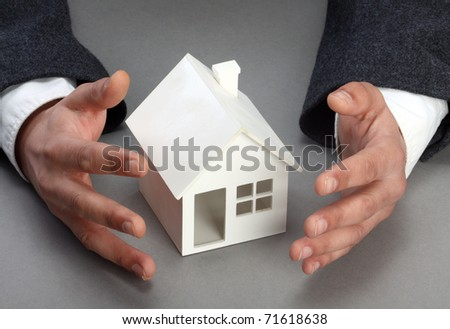 Hands and house model. Real property or insurance concept - stock photo