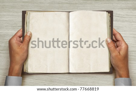 hands and opened vintage book over table - stock photo