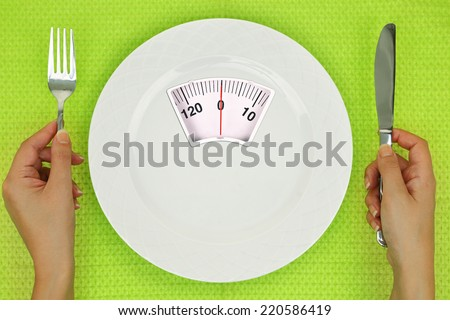Hands and plate with weighing scale on the table - stock photo