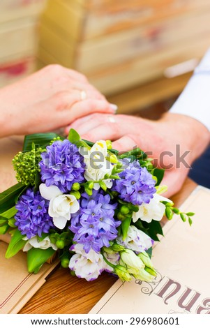 Hands and rings and beautiful wedding bouquet