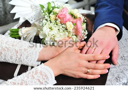 Hands and rings on wedding bouquet. Bride and groom's hands with wedding rings.  - stock photo