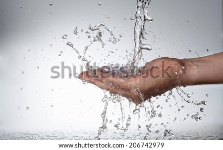 Hands and stream of water. On white background. High resolution. - stock photo