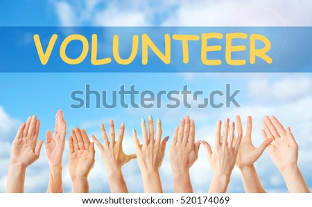 Hands and word VOLUNTEER on blue sky background. Help and support concept.