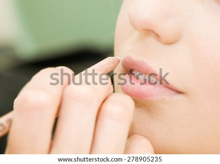 hands applying make up on a woman head - stock photo