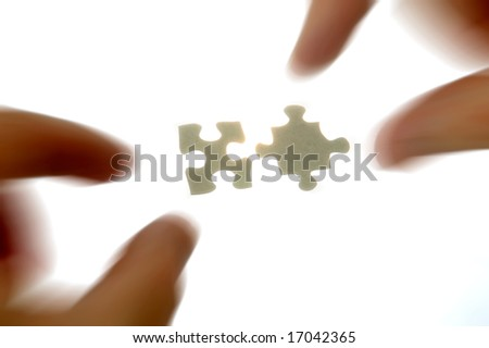 hands approaching two puzzle pieces with radial blur - stock photo