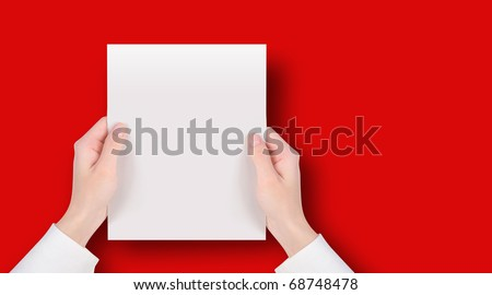 Hands are holding a blank white piece of paper on a red background. Add your text message easily. - stock photo