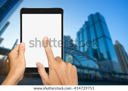 Hands are holding and touch Small Tablet Computer with office building background - stock photo