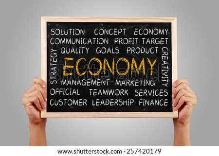Hands are holding the blackboard of economy word cloud with gray background. - stock photo