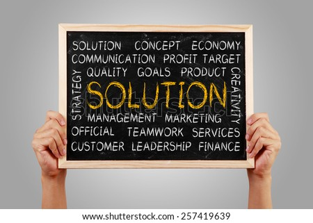 Hands are holding the blackboard of Solution word cloud with gray background. - stock photo