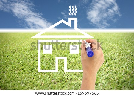 Hands are painted house on grass and empty space in concept  to create home.