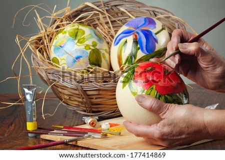 Hands are painting flowers on ostrich eggs . Easter decorations - stock photo