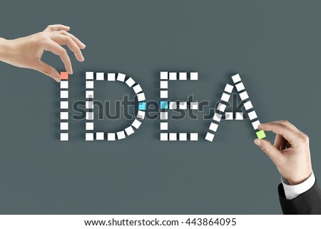 Hands arranging word idea with small cubes on dark grey background. Idea concept - stock photo