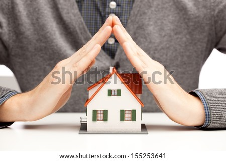 Hands as a protecting roof over a little house over white - stock photo