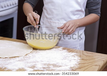 hands beating eggs on the kitchen table - stock photo