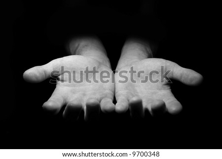 Hands begging alms on a black background - stock photo