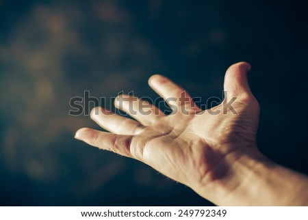 hands begging on a brown background - stock photo
