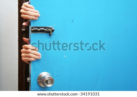 Hands behind a blue door - stock photo