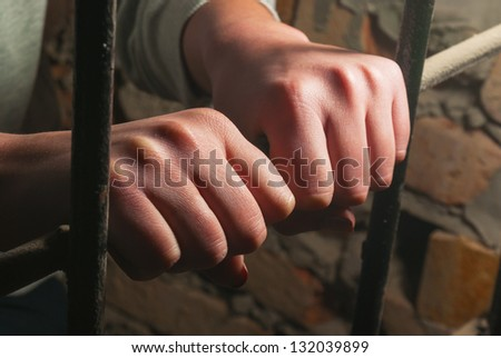 Hands behind the bars against the brick wall - stock photo