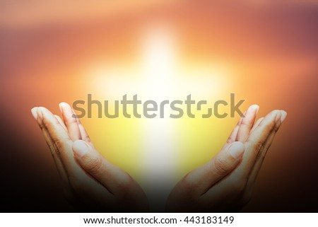Hands bless the cross in the sky. - stock photo