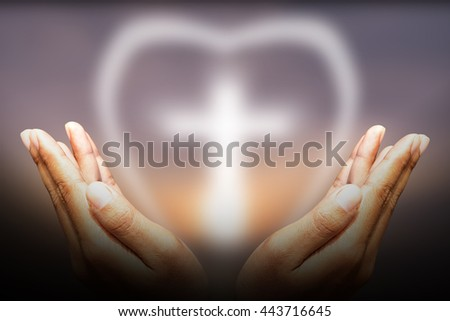 Hands bless the cross in the sunset sky. - stock photo
