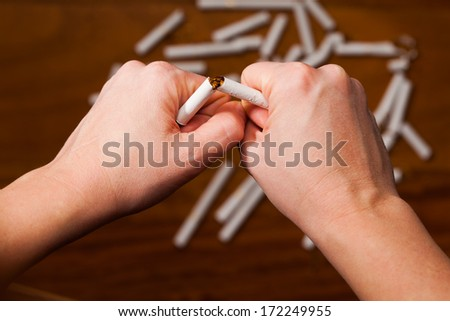 hands breaking a cigarette - give up smoking concept - stock photo