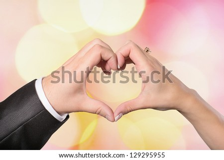 Hands bride and groom in a heart shape on a colored background defocused - stock photo