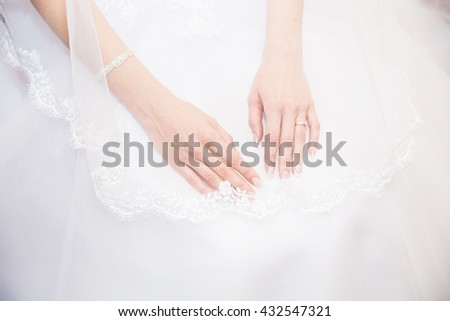 Hands bride with a manicure, on the finger of the bride wedding ring, hands on the background of white lace dress covered with a veil in studio.