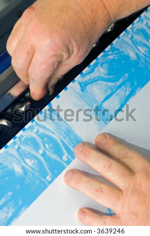 Hands calibrating the alignment of the cliches of an offset printing process / press - stock photo