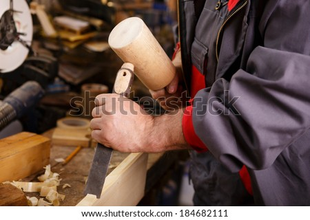 Hands carver at work with a wooden hammer and chisel