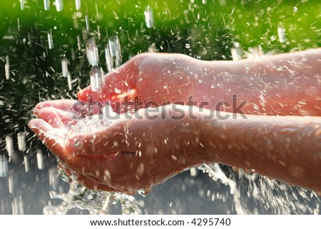Hands catching clean falling water close up. Environmental concept. - stock photo