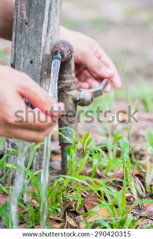 hands catching water from a tap in hands in garden - stock photo