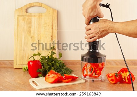 Hands chefs are going to shred red pepper in a blender - stock photo