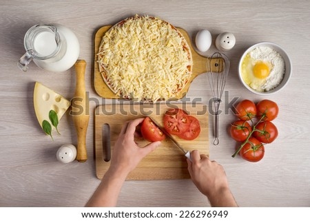 hands chefs cut tomatoes, cooking pizza ingredients on wooden background texture - stock photo
