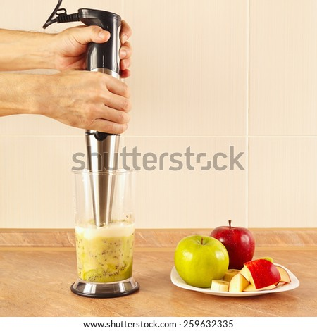 Hands chefs prepared fruit cocktail in the blender - stock photo