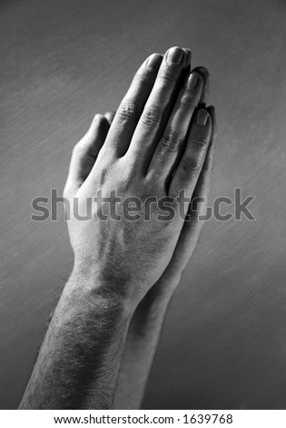 Hands clasped in a prayer. - stock photo