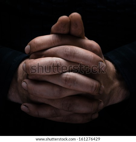 Hands clasped in Waiting, Black Background.