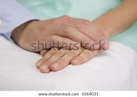 Hands clasping on hospital bed.
