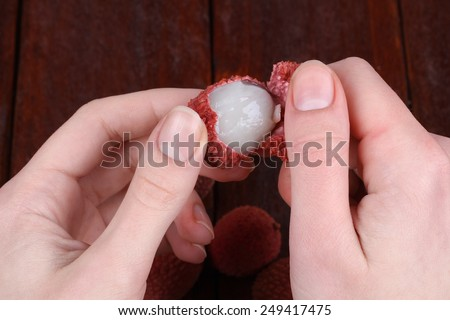 Hands, cleaning litchi from the shell. Tasty and delicious lychee fruit. Chinese plum, Litchi chinensis - stock photo