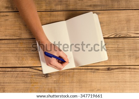 Hands close-up book to use notes on a wooden table - stock photo