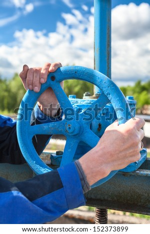 Hands close-up of mature manual worker turning stop-gate valve - stock photo