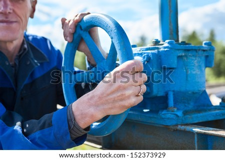 Hands close-up of senior manual worker turning cut-off valve at plant - stock photo