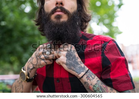 Hands close up of young tattooed man portrait in a park. Shoreditch borough, London. Hipster style. - stock photo