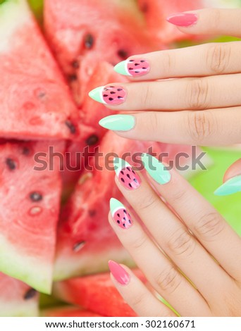 Hands close up of young woman with watermelon manicure and fruit, summer manicure nail art and food concept  - stock photo