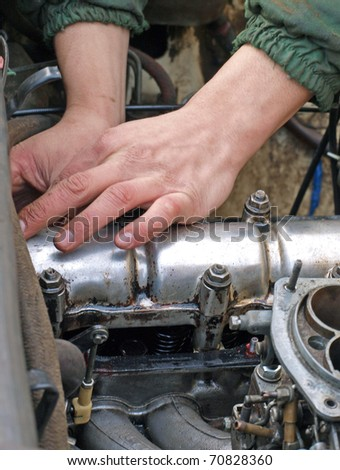 Hands close up, repairing old car engine