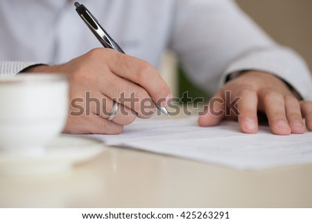 HANDS CLOSE-UP reviewing documents.Businessman sitting at desk having coffee break, sign documents. - stock photo