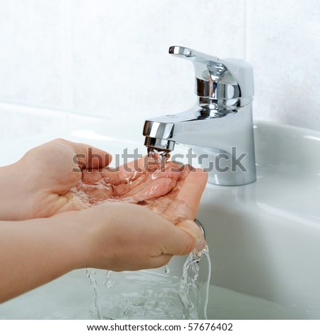 hands close-up with flowing water - stock photo