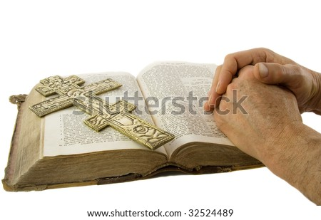 Hands closed in prayer and cross on an open bible isolated white - stock photo