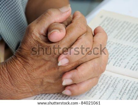 Hands closed praying on open bible - stock photo