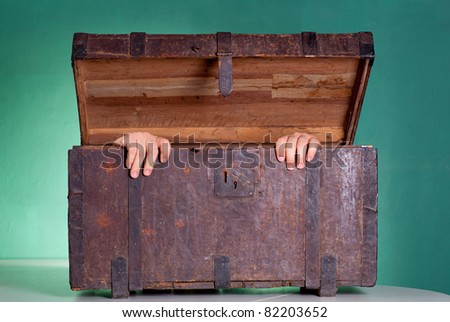 Hands coming out the Antique wooden trunk - stock photo